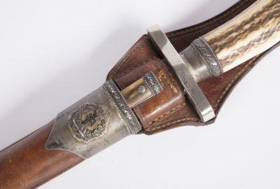 20 századi vadásztőr bőr tokkal, agancs markolattal, ezüstözött veretekkel.